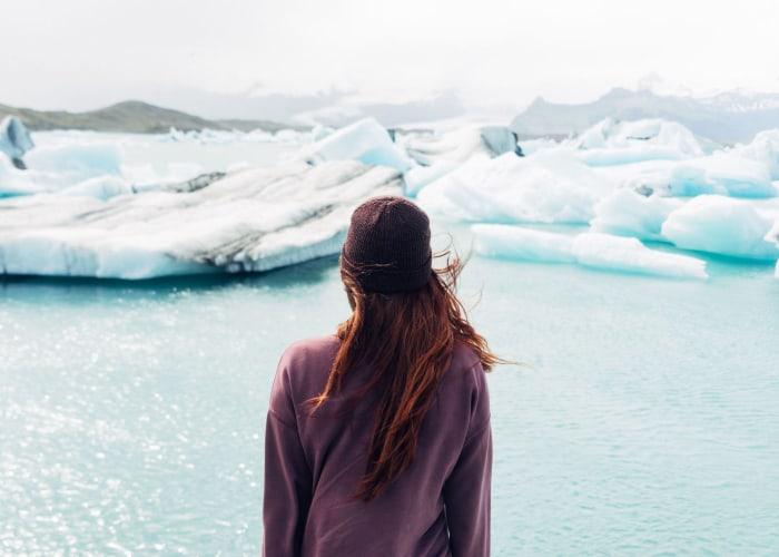 chica mirando un icerbeg derritiendose